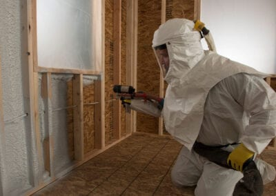 Austin Company | worker in protective gear installing spray foam insulation
