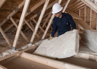 Austin Company | installing fiberglass in attic of residential home