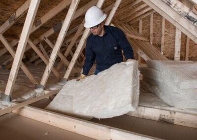 Austin Company | worker installign white fiberglass in attic of home