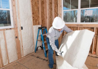 Austin Company | worker installing fiberglass in walls of home