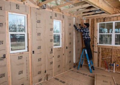 Austin Company | worker installing white fiberglass insulation